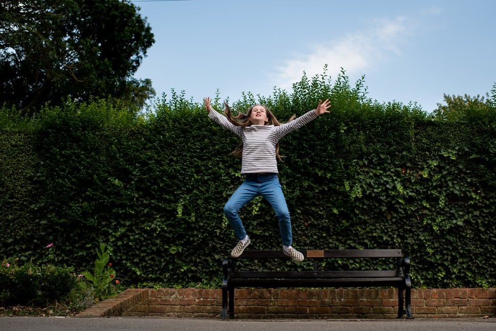 teen jumping off park bench happy