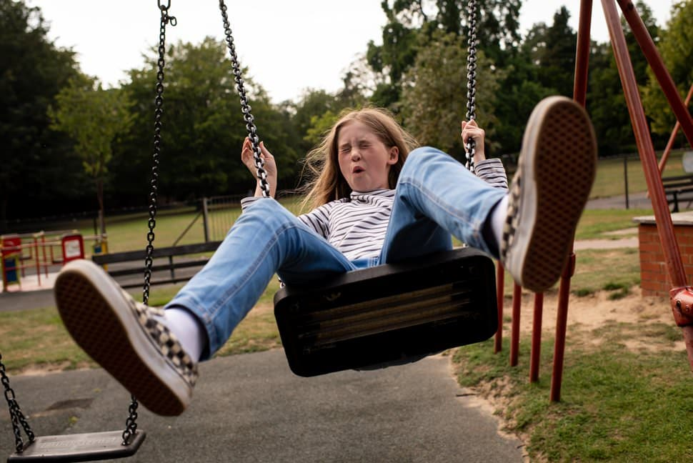 teenager uses swing in park pulls funny face