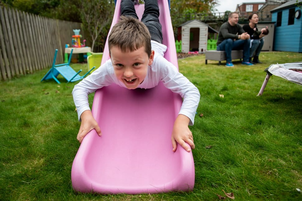 tween goes head first down slide in garden