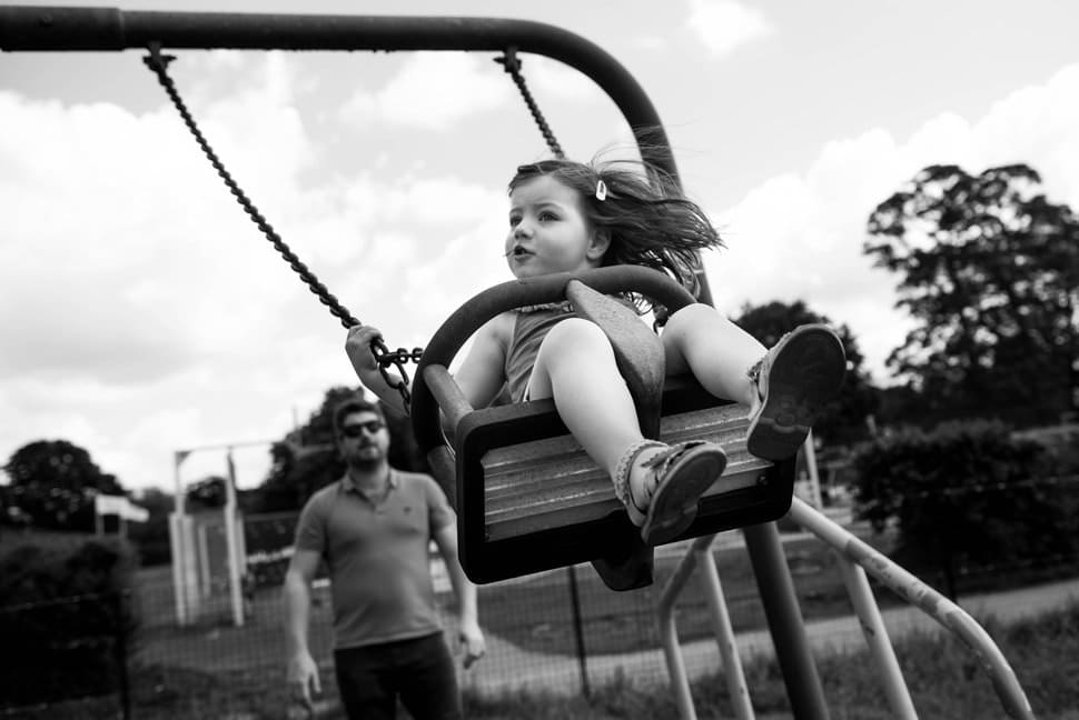 girl with hair flying uses swing in st albans family photoshoot