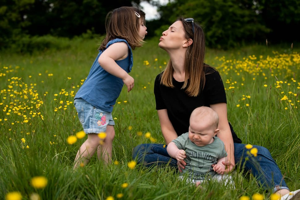 daughter and mum kiss in clover field in st albans