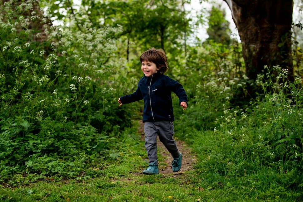 boy running through summer flowers in St Albans