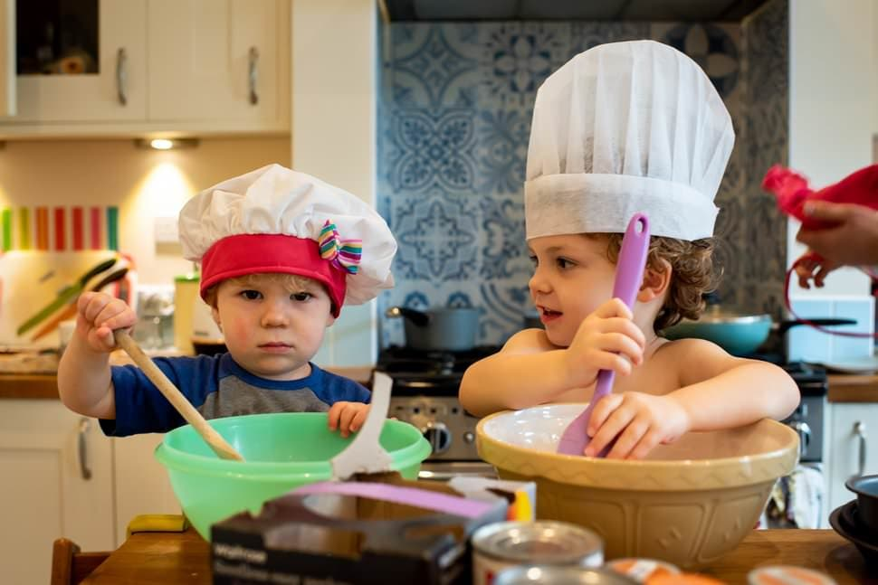 two little chefs cooking during home family photoshoot