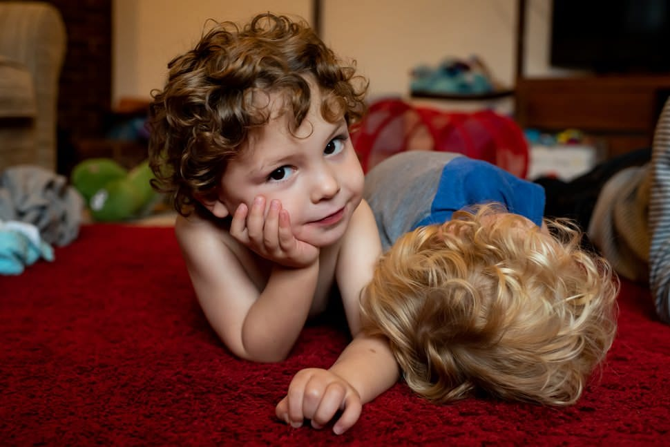 cute curly haired boy lying on carpet with brother