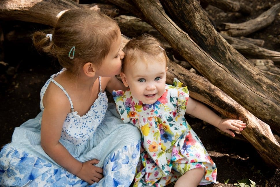 big sister kissing little sister in woods during St Albans family photos