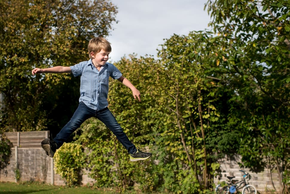 boy doing trampoline star jumps during family photoshoot