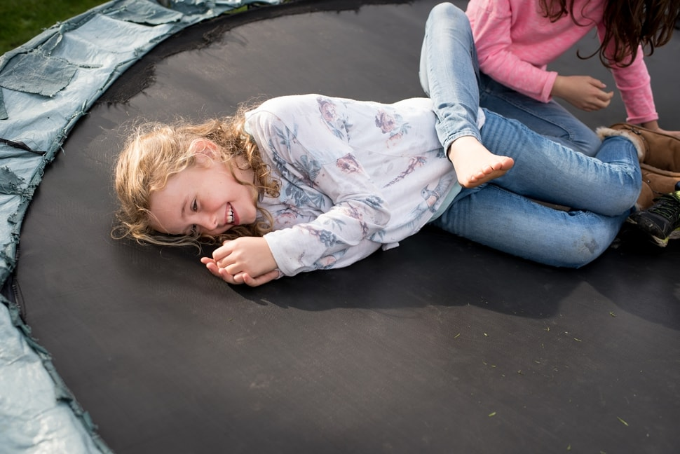 sisters playing on trampoline during west london family photo session