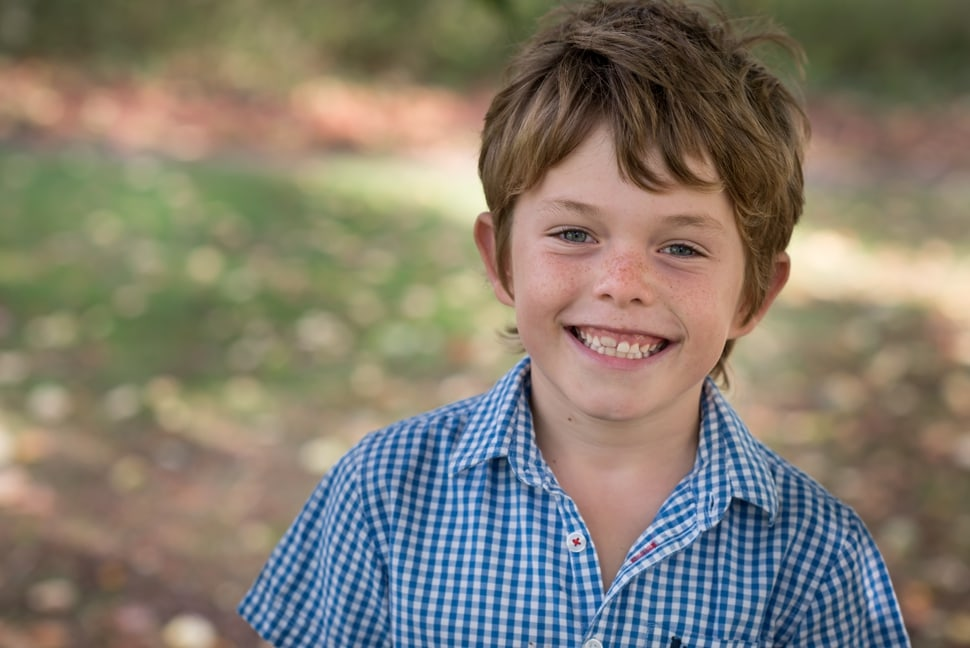 portrait of boy just getting first big tooth through
