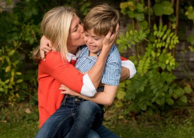 son getting big kisses from mum in sunshine during family photoshoot