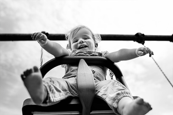 Welwyn family photographer, toddler on swing, family photo session