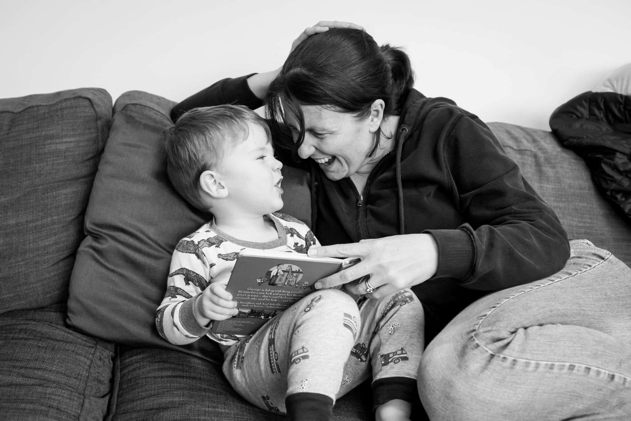 Tori Deslauriers photographer reading a book with her son on the sofa