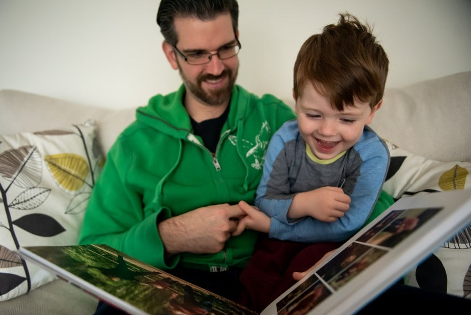 father and son look through photo scrapbook