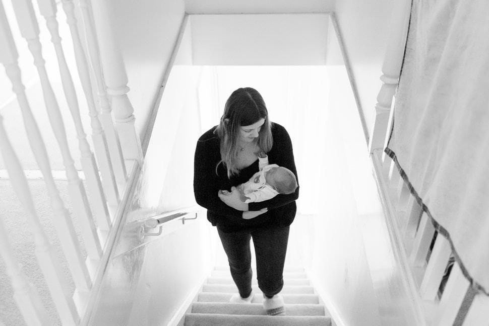 mum carrying newborn baby upstairs