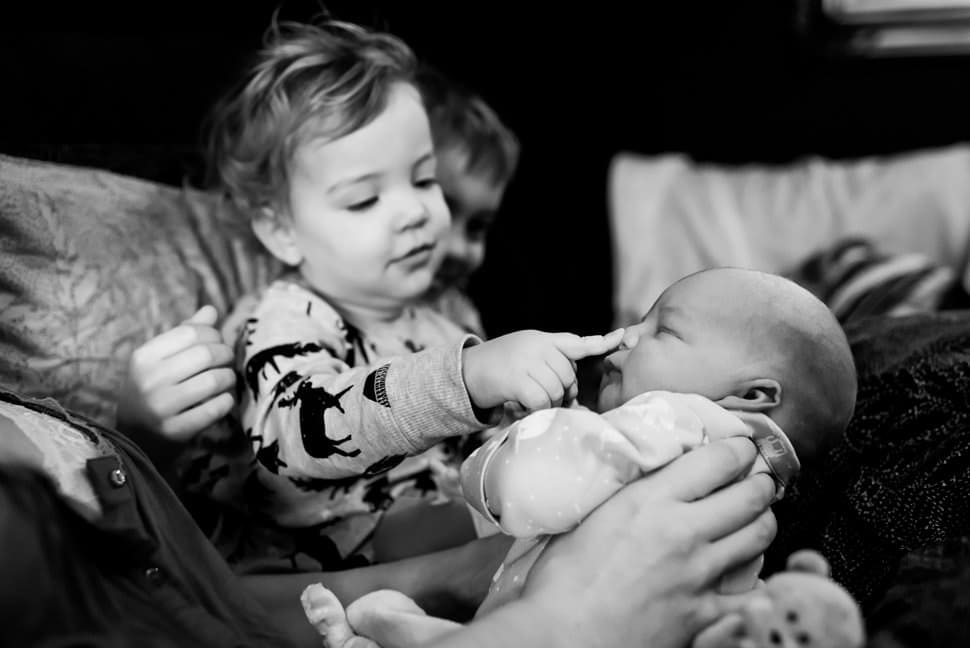 big sister squishing new baby brother nose fresh 48
