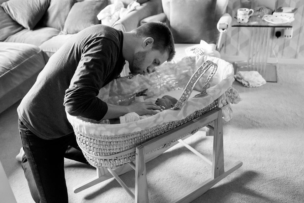 dad settling baby into bassinet