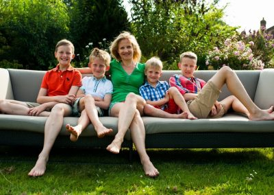 mother and four sons relaxing on garden sofa
