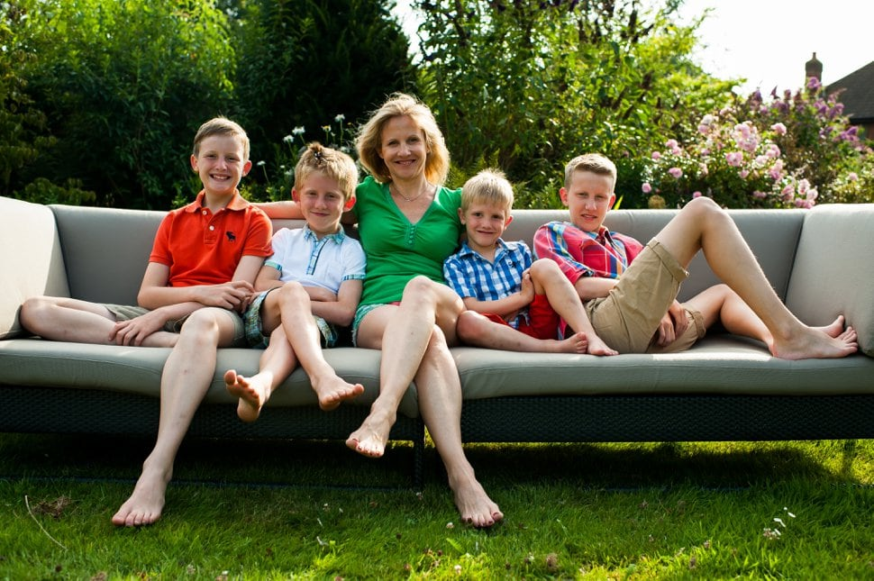 mother and four sons relaxing on garden sofa in Hertfordshire