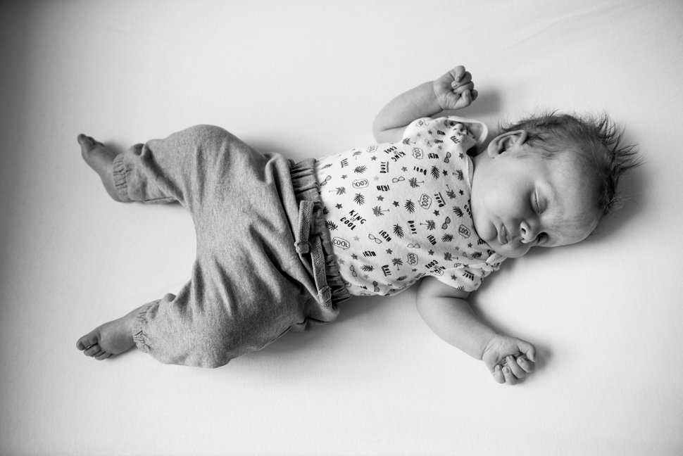 newborn baby fast asleep on back in cot