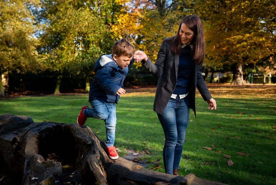 mum helps son climb a fallen tree in st albans park