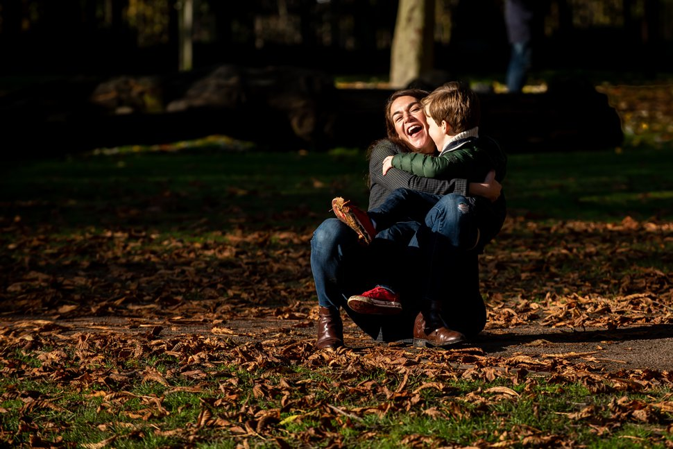 son knocks mum over with a huge cuddle during a St Albans park family photoshoot