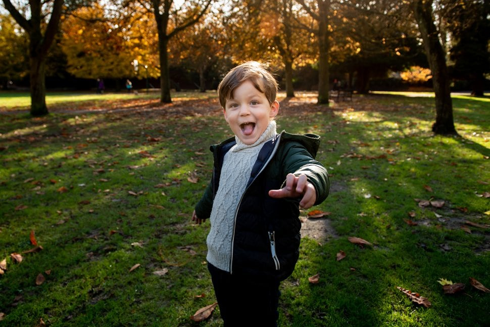little boy pulling funny face during autumn family photo session