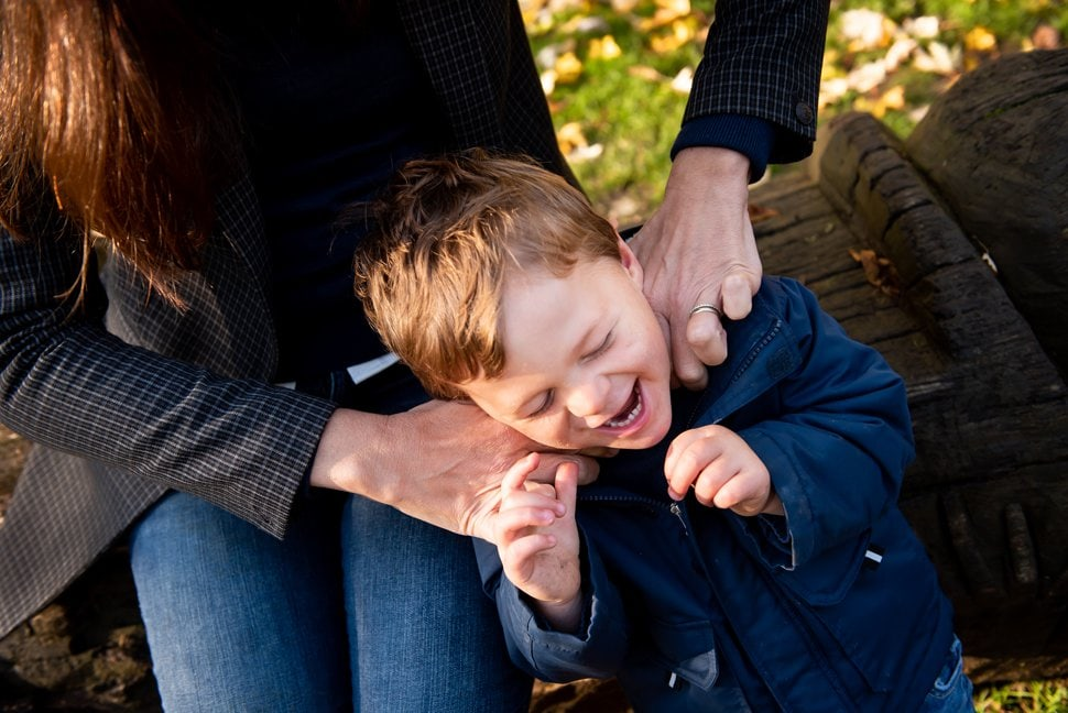 mum's hands ticking giggling son on his neck