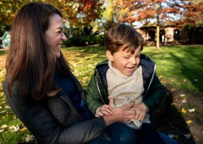 mum tickles her son in the tummy in St Albans park