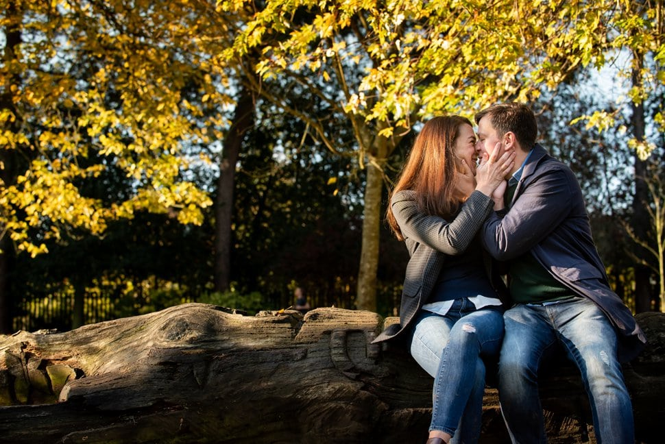 mum and dad kissing on a fallen tree seat in Clarence Park