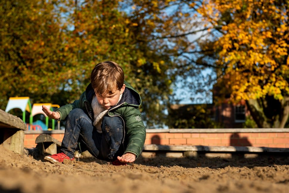little boy playing in a sandpit during autumnal family photoshoot