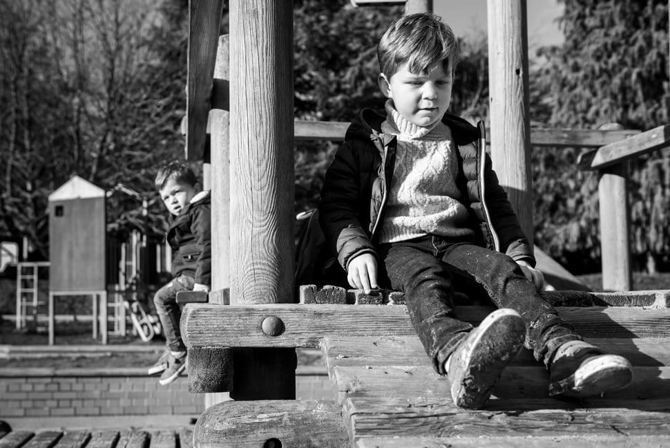 two brothers playing on wooden climbing frame in Clarence Park, St Albans