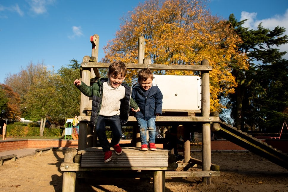 brothers hold hands and jump from wooden climbing frame in St Albans photoshoot