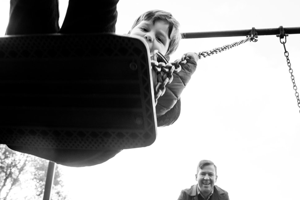 boy playing on a swing with dad during family photoshoot