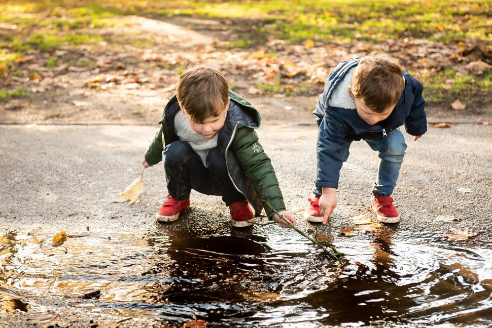 brothers playing with sticks in a muddy puddle