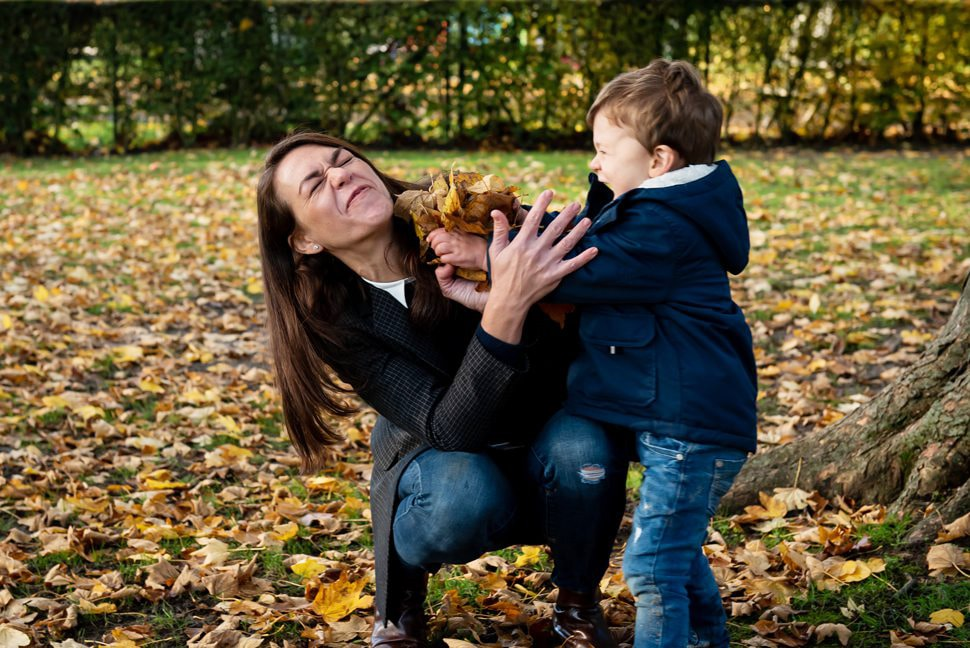 mum and son play fight in leaves at Clarence Park, St Albans