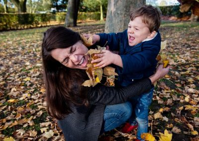 mum and son having a leaf fight during family photo shoot in St Albans
