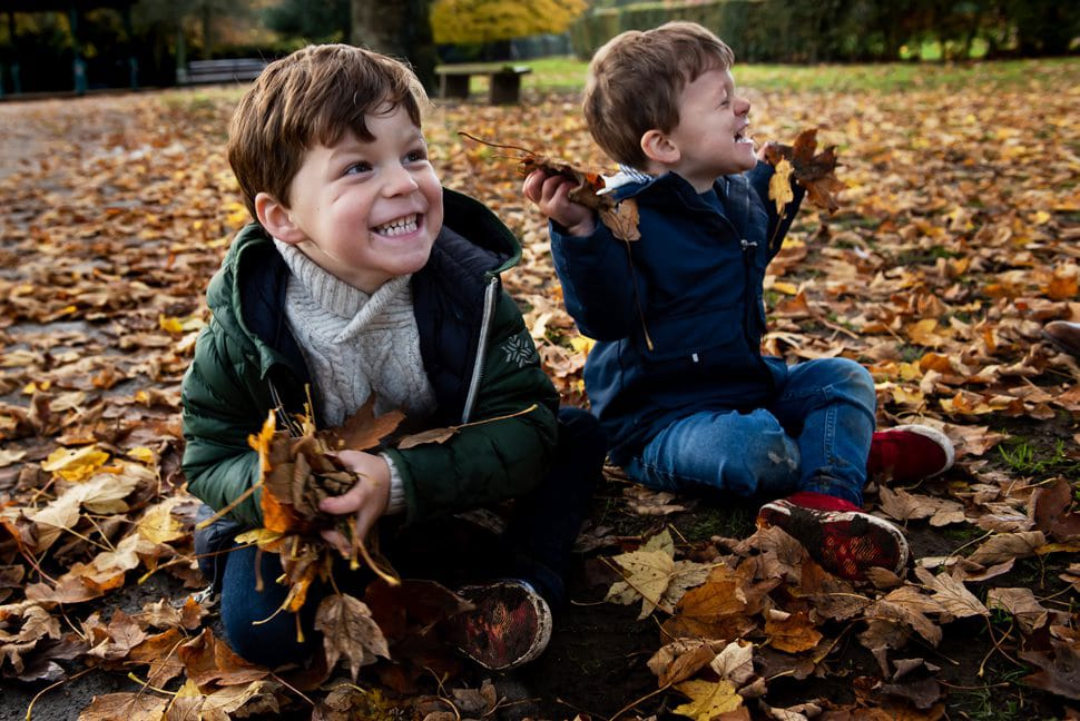brothers getting handfuls of leaves ready for leaf fight during family photoshoot