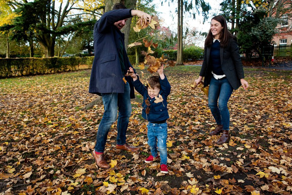 family leaf fight with raining leaves during family photo session St Albans