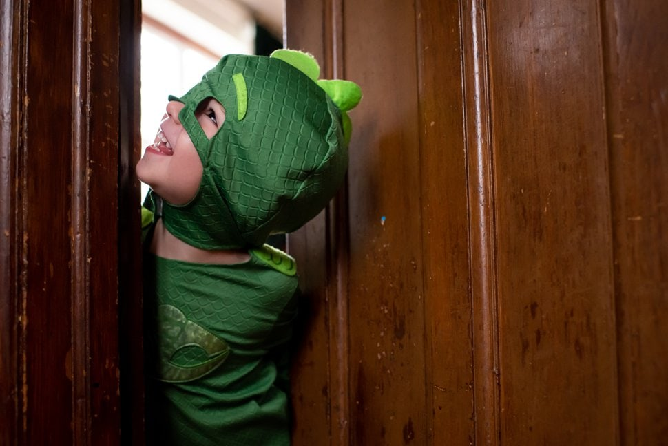 little boy in fancy dress hides behind wooden door