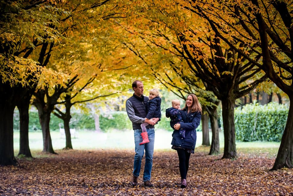 family walk through autumn trees on photoshoot