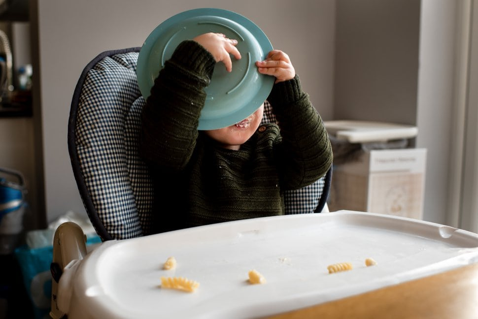 baby licking his plate in a highchair at home in st albans