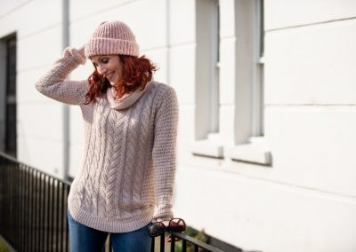 laughing girl in cable knit jumper and hat during corporate shoot