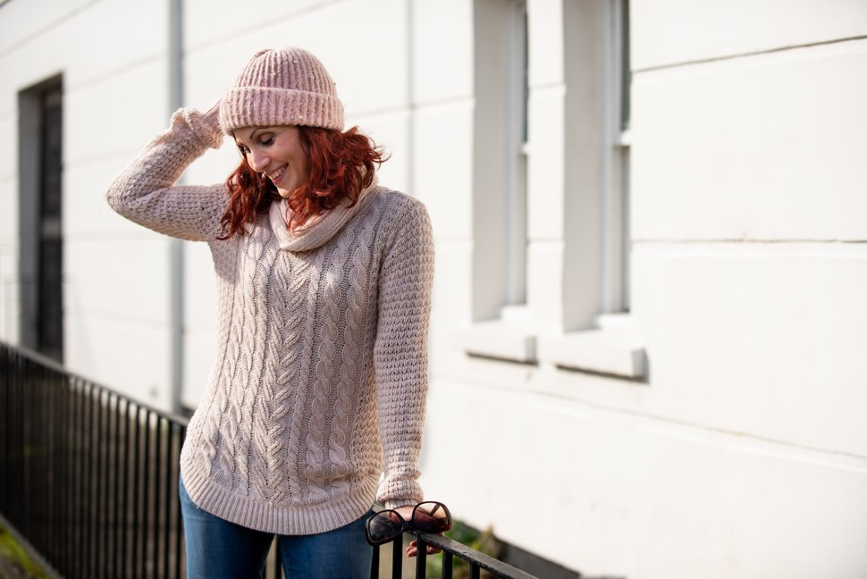 laughing woman in knitted jumper and hat